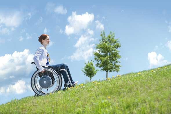 Frau fährt im Rollstuhl einen hang hinauf