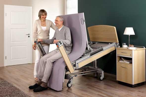 älterer Mann wird von seinem Pflegebett in eine stehende Position gebracht